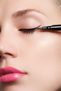 Beautiful woman with bright make up eye with sexy black liner makeup. Fashion arrow shape. Chic evening make-up. Makeup beauty wit Royalty Free Stock Photo