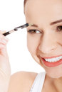 Beautiful woman brushing her eyebrow close up Stock Photo