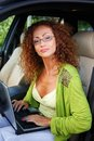 Beautiful woman in car with laptop middle aged redhead behind steering wheel Stock Photography