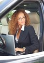 Beautiful woman in car middle aged redhead businesswoman black jacket with laptop behind steering wheel Stock Image