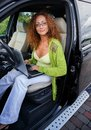 Beautiful woman in car middle aged redhead with laptop behind steering wheel Stock Photo