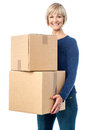Beautiful woman carrying cardboard boxes cheerful posing with two packed Royalty Free Stock Photo