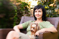 Beautiful woman in chair with little dog in garden Royalty Free Stock Photo