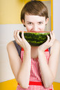Beautiful woman chewing on a ripe juicy watermelon in bright yellow house interior Royalty Free Stock Images