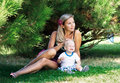 Beautiful woman with a child sitting on the grass Stock Photos