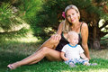 Beautiful woman with a child sitting on the grass Royalty Free Stock Image