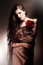 Beautiful woman in chocolate fabric blue with red rose Stock Photo