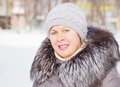 Beautiful woman in a coat with fur collar and a knitted hat Royalty Free Stock Photo