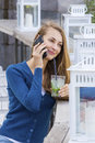 Beautiful Woman with cocktail in cafe mobile phone speaking. Royalty Free Stock Photo