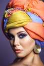 Beautiful woman with colored headwear and blue makeup. Royalty Free Stock Photo