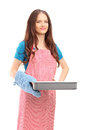 Beautiful woman with cooking mittens and apron holding a baking tray isolated on white background Royalty Free Stock Images