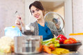 Beautiful woman cooking veggie soup with laddle in kitchen at home Stock Photos