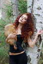 Beautiful woman in corset with fur dreams near birch Royalty Free Stock Photo