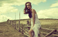 Beautiful woman in the countryside a white dress sat on a wooden fence a field with a cloudscape background Stock Photos