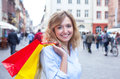 Beautiful woman with curly blond hair and shopping bags in the city