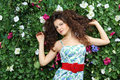Beautiful woman with curly hair stands next to green hedge in garden Stock Image