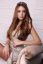 Beautiful woman with dark hair wears elegant dress and precious crown Royalty Free Stock Photo