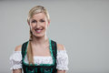 Beautiful woman in a dirndl head and shoulders portrait of young with her blond hair braid wearing traditional bavarian on Stock Photos
