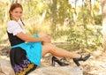 Beautiful Woman in Dirndl Posing on Fallen Tree Royalty Free Stock Photo