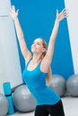 Beautiful woman doing aerobics in a gym stretching her arms muscles with lovely friendly smile against backdrop of pilates Royalty Free Stock Photo