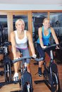 Beautiful woman doing exercise in a spinning class women at gym Stock Images