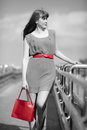 Beautiful woman in dress with red shopping bag and belt walking on the bridge Royalty Free Stock Images