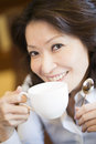 Beautiful woman drink coffee read newspaper front window Royalty Free Stock Image