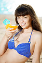 Beautiful woman with a drink in hand on the beach sun Stock Photo