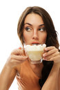 Beautiful woman drinking cappuccino coffee looking Stock Images