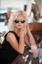 Beautiful woman drinking coffee in cafe restaurant girl in bar summer vacation pretty blond at breakfast happy smiling woman with Royalty Free Stock Photos