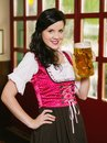 Beautiful woman drinking oktoberfest beer photo of a wearing traditional dirndl and a huge Royalty Free Stock Photography