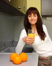 Beautiful woman drinking orange juice in kitchen Royalty Free Stock Images