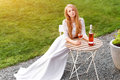 Beautiful woman drinking wine in outdoors cafe. Portrait of young blonde beauty in the vineyards having fun, enjoying a Royalty Free Stock Photo