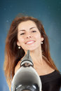 Beautiful woman drying her hair with hairdryer young over misty blue background Royalty Free Stock Images