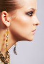Beautiful woman in ear rings sideview portrait of young brunette on gray Stock Image