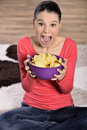 Beautiful woman eating junk food potato chips crisps cute having a snack while Royalty Free Stock Image