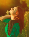 Beautiful woman enjoy sunshine in summer day on yellow background girl looking up with closed eyes Stock Image