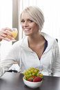 Beautiful woman enjoying a healthy breakfast of fresh fruit and juice sitting at table smiling at the camera Royalty Free Stock Photography
