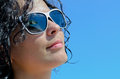 Beautiful woman enjoying the sun wearing trendy modern sunglasses with her head tilted back into sunshine against a blue sky Royalty Free Stock Photography