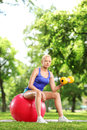 Beautiful woman exercising in a park with a ball and dumbbell young Royalty Free Stock Image