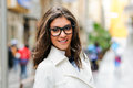 Beautiful woman with eye glasses smiling in urban background Stock Images