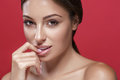 Beautiful woman face touching her lips by fingers close up studio portrait on red Royalty Free Stock Photo