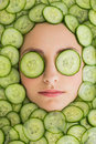 Beautiful woman with facial mask of cucumber slices on face close up a young her at spa salon Stock Photo
