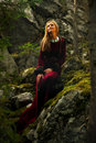 Beautiful woman fairy with long blonde hair on rocks amids a in a historical gown is standing Royalty Free Stock Images