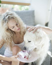 Beautiful woman feeding cake to dog in house Royalty Free Stock Photo
