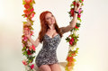 Beautiful woman in the floral swing redhaired Stock Image