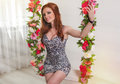 Beautiful woman in the floral swing redhead Royalty Free Stock Image