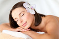 Beautiful woman with flower in her hair in spa health beauty resort and relaxation concept salon lying on the massage desk Stock Photo
