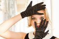 Beautiful woman framing her blue eyes with Black gloves Royalty Free Stock Image