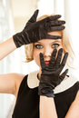 Beautiful woman framing her blue eyes with Black gloves Royalty Free Stock Photography